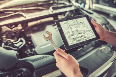 Cropped image of auto mechanic in uniform using a digital tablet and a spanner while repairing car in auto service