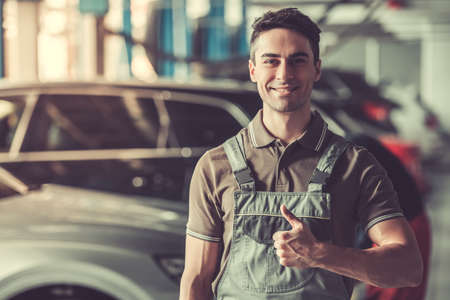 Attractive young auto mechanic in uniform is showing Ok sign, looking at camera and smiling while standing in auto service