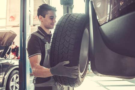 Il giovane meccanico bello in uniforme sta cambiando una gomma mentre lavorava nel servizio automatico