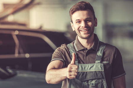 De knappe jonge automonteur in eenvormig toont Ok teken, bekijkt camera en glimlacht terwijl status in de autodienst