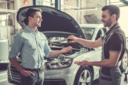 At the auto service. Handsome young auto mechanic in uniform is returning car key to a client, both are smiling