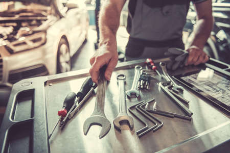 Cropped image of handsome young auto mechanic in uniform choosing tools for repairing car in auto service Standard-Bild