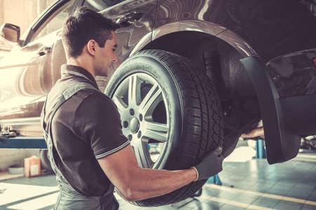 Il bel giovane meccanico auto in uniforme sta cambiando un pneumatico mentre lavora nel servizio auto