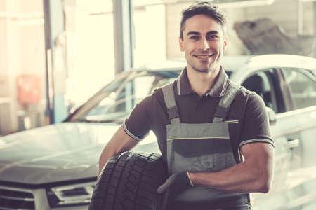 Al servizio auto. Bel giovane auto meccanico in uniforme è in possesso di un pneumatico, guardando la fotocamera e sorridente