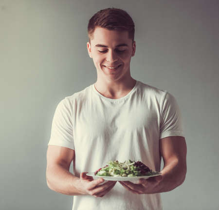 Handsome guy is smiling while holding a plate with salad, on gray background