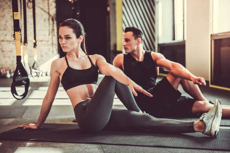 Beautiful young sports couple is stretching after workout in gym Stok Fotoğraf
