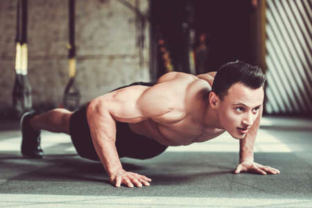 Handsome young muscular sportsman is doing push-ups while working out in gym Stock Photo