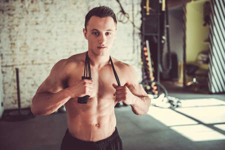 Handsome young muscular sportsman is holding a jumping rope and looking at camera while standing in gym
