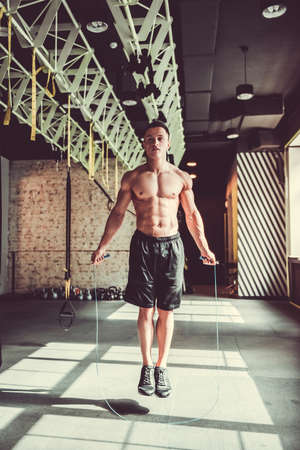 Handsome young muscular sportsman is jumping with a skip rope while working out in gym Stock Photo