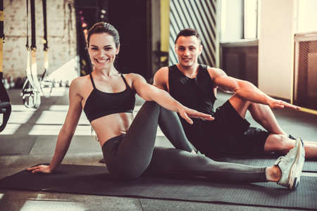 Beautiful young sports couple is stretching after workout in gym Foto de archivo