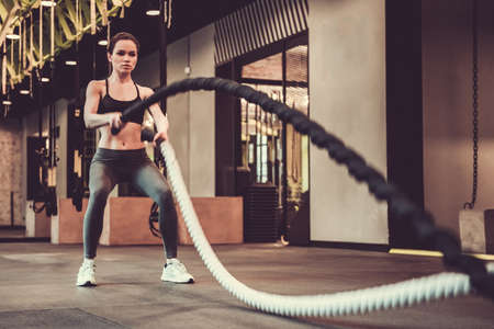 Beautiful sports girl is doing battle rope exercise while working out in gym Stock Photo