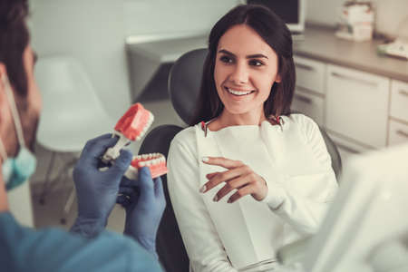 Beautiful woman is sitting in dentists chair and listening to the doctor Stock Photo