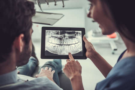 Handsome young patient and beautiful female dentist are looking at teeth image on a digital tablet