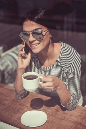 The view through the window. The young beautiful girl drinking coffee while sitting in a cafe and emotionally talking on the phone Stock Photo