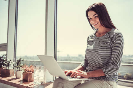 Cheerful young pretty girl using laptop while sitting on the windowsill in the cafe.
