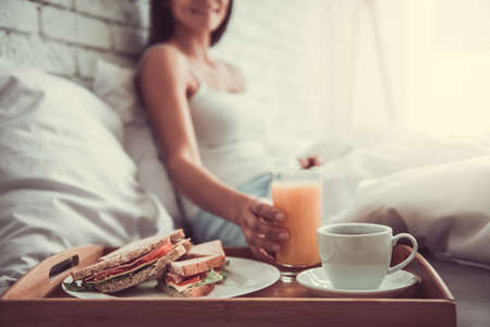 hotel bedroom: Good morning! Happy young beautiful woman eating breakfast while sitting on the bed at home