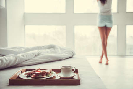 Good morning! Happy young beautiful woman awaiting breakfast in bed in her bedroom