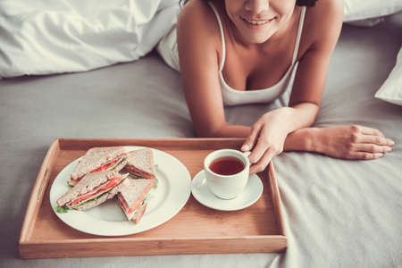 Good morning! Happy young beautiful woman eating breakfast while sitting on the bed at home
