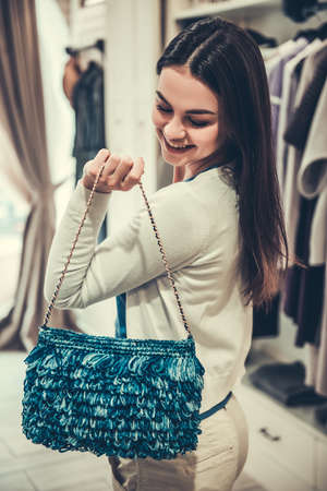 Beautiful girl is choosing a reticule and smiling while doing shopping in boutique
