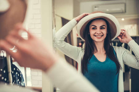 Beautiful girl is choosing a hat, looking into the mirror and smiling while doing shopping in boutique Stock Photo