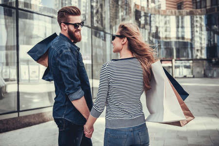 holding hands while walking: Beautiful young couple in sun glasses and with shopping bags holding hands, looking at each other and smiling while walking down the street Stock Photo