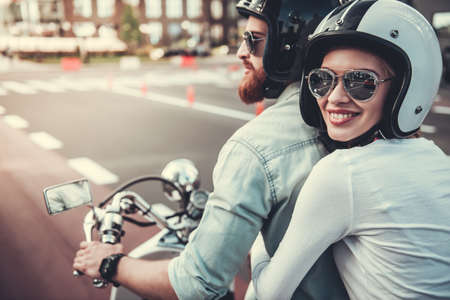 Beautiful young couple in sun glasses and helmets is smiling while riding a scooter