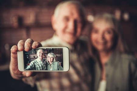 美しいシニア カップルはハグ、selfie スマート フォンを使用し、キッチンに立ちながら笑顔をしています。フォーカスを電話します。
