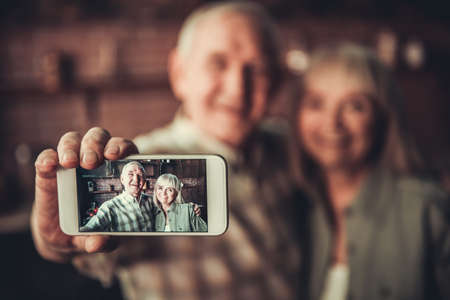 Beautiful senior couple is hugging, doing selfie using a smart phone and smiling while standing in kitchen. Phone in focus