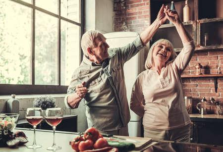 美しいシニア カップルのダンス、一緒にキッチンで料理をしながら笑みを浮かべて
