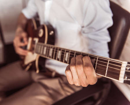 Cropped image of young businessman playing guitar in his office during the break