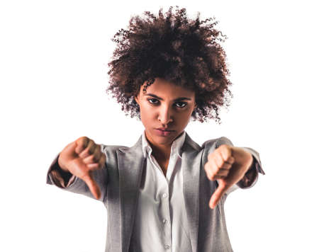 Beautiful young Afro American business woman in formal wear is showing thumbs down and looking at camera, isolated on white