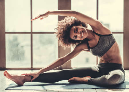 Attractive Afro American girl in sportswear is stretching, looking at camera and smiling Stock Photo