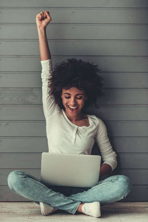 Attractive Afro American girl is using a laptop, raising hand in fist and smiling while sitting on the floor Standard-Bild