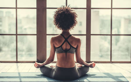 Back view of attractive Afro American girl in sportswear sitting in lotus position while doing yoga 스톡 콘텐츠