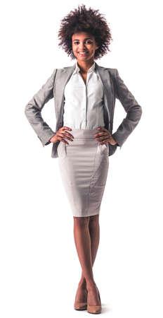 笑みを浮かべて立っている腰に当て、白の分離間正式な摩耗で美しい若いアフロ アメリカのビジネス女性の完全な長さの肖像画 写真素材