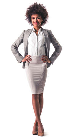 Full length portrait of beautiful young Afro American business woman in formal wear smiling while standing akimbo, isolated on white 版權商用圖片