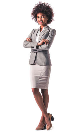Full length portrait of beautiful young Afro American business woman in formal wear smiling while standing with crossed arms, isolated on white Imagens