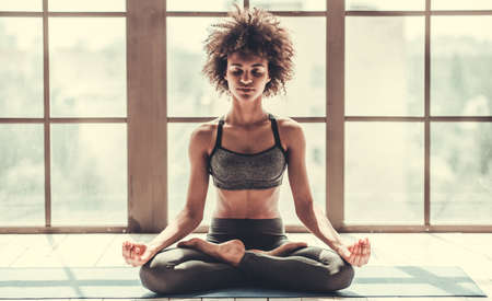 Attractive Afro American girl in sportswear is meditating while doing yoga 스톡 콘텐츠