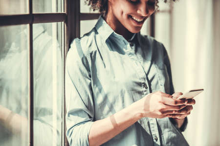 Beautiful Afro American girl in casual clothes is using a smart phone and smiling while standing near the window, cropped Stock Photo
