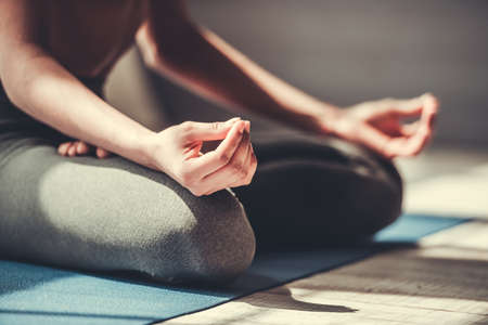 Cropped image of Afro American in sportswear meditating on yoga mat
