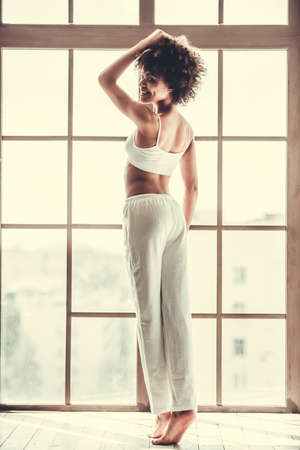 Full length portrait of beautiful Afro American girl in white home wear smiling while standing the window