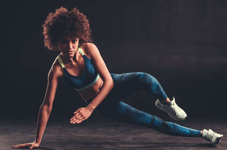 Attractive Afro American girl in sportswear is looking at camera while working out, on black background