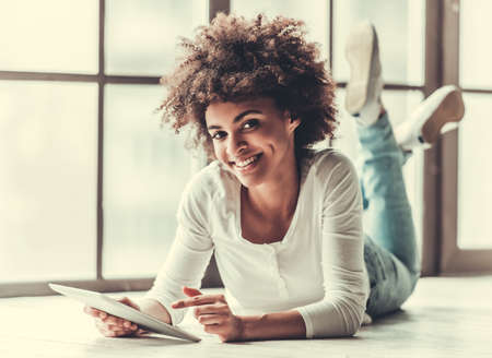 Attractive Afro American girl is using a digital tablet, looking at camera and smiling while lying on the floor Standard-Bild