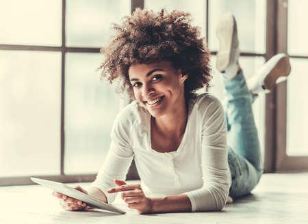 Attraktives afroes-amerikanisch Mädchen benutzt eine digitale Tablette, betrachtet Kamera und lächelt beim Lügen auf dem Boden