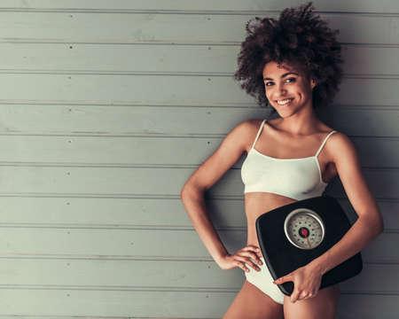 Het mooie Amerikaanse meisje van Afro in witte lingerie houdt weegt schalen, bekijkt camera en glimlacht, op grijze muurachtergrond
