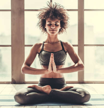 Attractive Afro American girl in sportswear is doing yoga and smiling Stockfoto