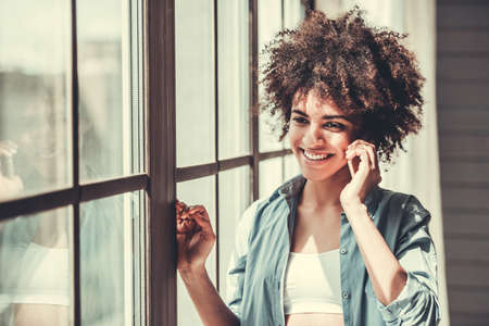 Beautiful Afro American girl in casual clothes is talking on the mobile phone and smiling while standing near the window