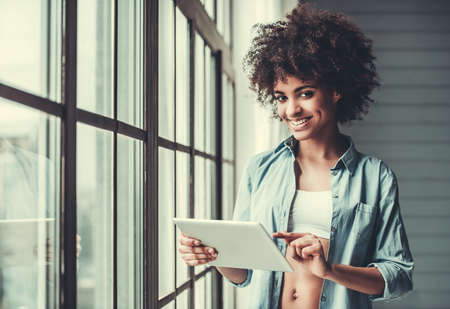 Beautiful Afro American girl in casual clothes is using a digital tablet, looking at camera and smiling while standing near the window