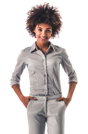 Beautiful young Afro American woman is looking at camera and smiling while standing with hands in pockets, isolated on white