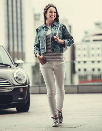 Volledig lengtebeeld van mooi meisje die in het jasje van Jean glimlachen terwijl het lopen van haar auto Stockfoto